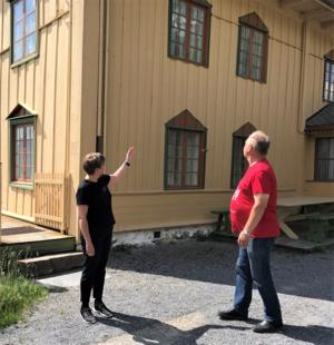 Museumsvert med gjest foran huset til Bjørnstjerne Bjørnson på Aulestad.