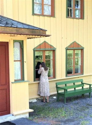 Dame som ser inn gjennom vinduene til Bjørnstjerne Bjørnsons hjem.