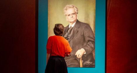 Dame studerer bilde av Bjørnstjerne Bjørnson i utstillingen Det volder litt rabalder.