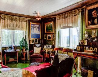 Stuen er tungt møblert med vakre møbler og mange bilder på veggene