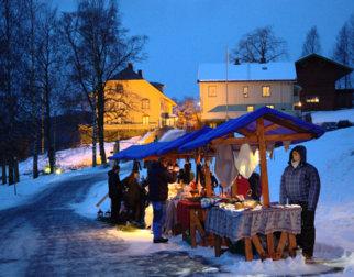 Salgsboder på tunet foran Bjørnstjerne Bjørnsons hjem Aulestad i tussmørket.