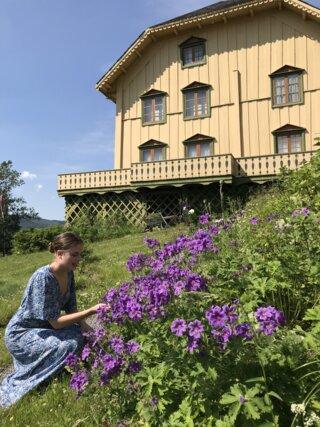 Dame som ser på blomstene i hagen til Bjørnstjerne Bjørnson.