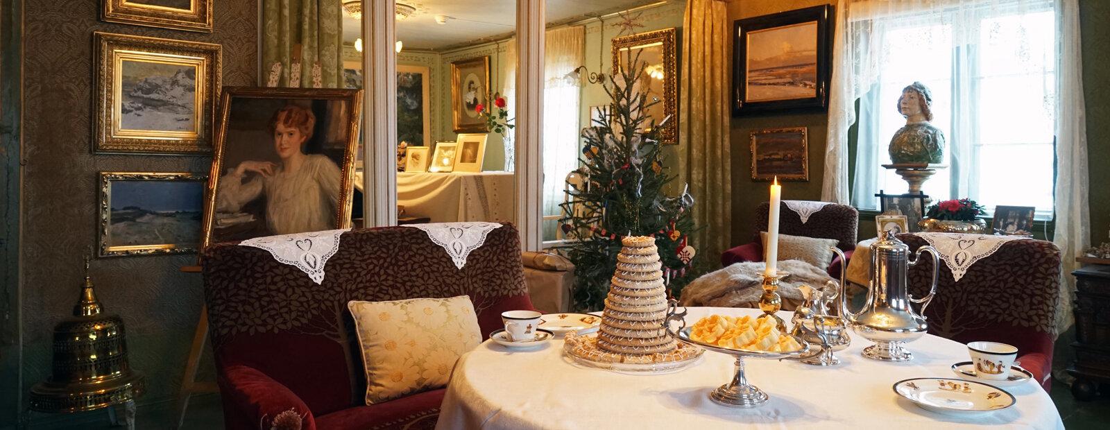 Bord dekket til jul med juletre i bakgrunnen.