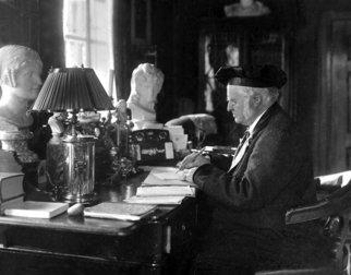 Bjørnstjerne Bjørnson sitter ved skrivebordet sitt.