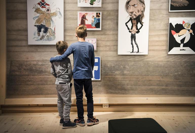 To barn studerer bilder på veggen med karikaturer.